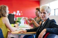 Concepteur féminin sûr s'asseyant à son bureau pour une séance de réflexion dans les bureaux créatifs rouges Photo libre de droits