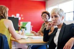 Concepteur féminin sûr s'asseyant à son bureau pour une séance de réflexion dans les bureaux créatifs rouges Image libre de droits