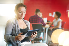 Concepteur féminin sûr travaillant à un comprimé numérique dans les bureaux créatifs rouges Photographie stock libre de droits