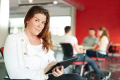 Concepteur féminin sûr travaillant à un comprimé numérique dans les bureaux créatifs rouges Images libres de droits