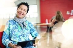 Concepteur féminin sûr travaillant à un comprimé numérique dans les bureaux créatifs rouges Image stock