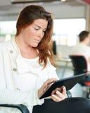 Concepteur féminin sûr travaillant à un comprimé numérique dans les bureaux créatifs rouges Photo stock