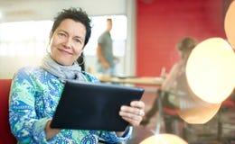 Concepteur féminin sûr travaillant à un comprimé numérique dans les bureaux créatifs rouges Photo libre de droits