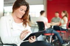 Concepteur féminin sûr travaillant à un comprimé numérique dans les bureaux créatifs rouges Photographie stock