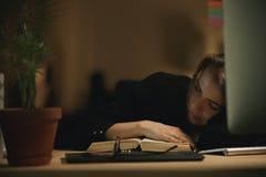 Concepteur fatigué de jeune dame dormant à l'intérieur la nuit sur le livre Photo libre de droits