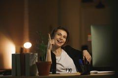Concepteur heureux de jeune dame s'asseyant dans le bureau la nuit Images libres de droits