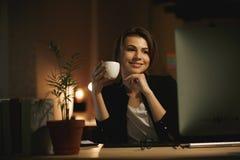 Concepteur heureux de jeune femme la nuit utilisant l'ordinateur Photographie stock libre de droits
