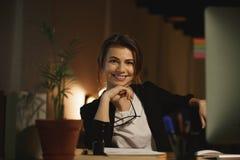 Concepteur heureux de jeune femme s'asseyant dans le bureau la nuit Photo stock