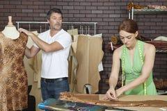 Concepteur masculin regardant le collègue comme elle trace le modèle sur le tissu dans le studio de conception Image stock
