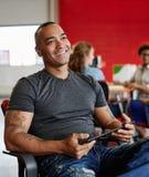 Concepteur masculin sûr travaillant à un comprimé numérique dans les bureaux créatifs rouges Photos libres de droits
