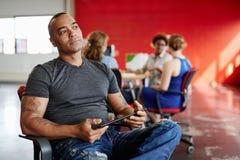 Concepteur masculin sûr travaillant à un comprimé numérique dans les bureaux créatifs rouges Photo libre de droits