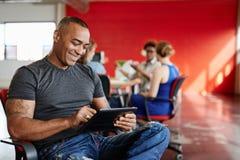Concepteur masculin sûr travaillant à un comprimé numérique dans les bureaux créatifs rouges Image stock
