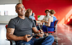 Concepteur masculin sûr travaillant à un comprimé numérique dans les bureaux créatifs rouges Photos stock