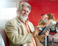 Concepteur masculin sûr travaillant à un comprimé numérique dans les bureaux créatifs rouges Photographie stock