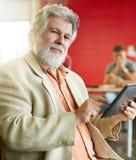 Concepteur masculin sûr travaillant à un comprimé numérique dans les bureaux créatifs rouges Photographie stock libre de droits