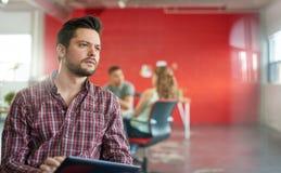 Concepteur masculin sûr travaillant à un comprimé numérique dans les bureaux créatifs rouges Images libres de droits