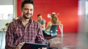 Concepteur masculin sûr travaillant à un comprimé numérique dans les bureaux créatifs rouges Images stock
