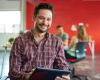 Concepteur masculin sûr travaillant à un comprimé numérique dans les bureaux créatifs rouges Image libre de droits