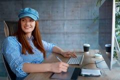 Concepteur moderne de femme souriant et travaillant sur le lieu de travail images libres de droits