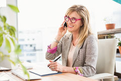 Concepteur occasionnel de sourire ayant un appel téléphonique Photographie stock