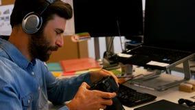 Concepteur regardant l'appareil photo numérique dans le bureau créatif banque de vidéos