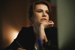 Concepteur sérieux de jeune dame s'asseyant dans le bureau la nuit Image stock