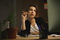 Concepteur sérieux de jeune dame s'asseyant dans le bureau la nuit Photo stock