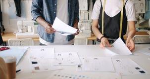 Concepteurs de vêtements travaillant avec des croquis mettant des papiers sur le pointage de table clips vidéos