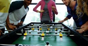 Concepteurs heureux jouant le football de table banque de vidéos