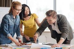 Concepteurs heureux positifs se tenant autour de la table Photos stock