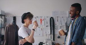 Concepteurs homme et café à emporter potable parlant de détente de femme dans le studio clips vidéos