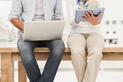 Concepteurs occasionnels s'asseyant sur le bureau en bois et à l'aide des dispositifs Photos stock