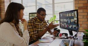 Concepteurs travaillant aux photos au-dessus de l'ordinateur au bureau dans le bureau 4k clips vidéos