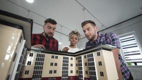 Concepteurs travaillant avec la maquette de la maison photographie stock libre de droits