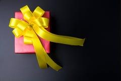 Conception actuelle de boîte-cadeau enveloppée en papier de couleur avec des arcs sur un bl photo stock