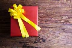 Conception actuelle de boîte-cadeau enveloppée en papier de couleur avec des arcs sur un OE Images stock