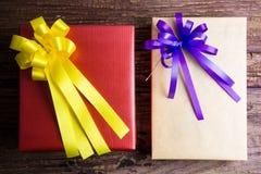 Conception actuelle de boîte-cadeau enveloppée en papier de couleur avec des arcs sur un OE Photo stock
