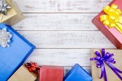 Conception actuelle de boîte-cadeau enveloppée en papier de couleur avec des arcs sur un wh Images stock