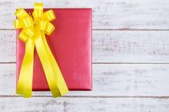 Conception actuelle de boîte-cadeau enveloppée en papier de couleur avec des arcs sur un wh Image stock