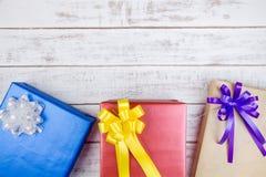 Conception actuelle de boîte-cadeau enveloppée en papier de couleur avec des arcs sur un wh Image libre de droits