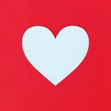 conception de couper le coeur de livre blanc sur le fond de papier rouge Image stock
