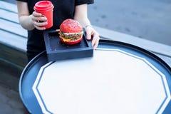 Conception de prêt-à-manger avec la fille mangeant l'hamburger Photographie stock libre de droits