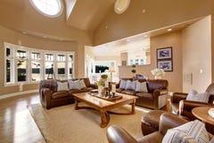 Conception intérieure de grand salon avec le plafond voûté haut et l'ensemble en cuir brun de sofa images stock