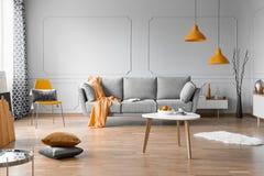 Conception intérieure de salon à la mode avec le divan gris, la table basse en bois et les accents oranges images stock