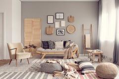 Conception intérieure de salon élégant avec le canapé scandinave, le mur gris et les accents naturels image libre de droits