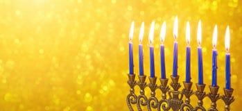 Conception juive de bannière de site Web de Hanoucca de vacances avec le menorah et bougies au-dessus de bokeh d'or Photographie stock