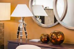 Conception moderne de pièce hest des tiroirs avec une lampe de table sur un trépied, vases décoratifs ronds de cuivre photos libres de droits
