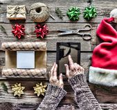 Conception : Préparation des cadeaux de Noël Un homme tient une tablette dans des ses mains et emballe des cadeaux de Noël Photos stock