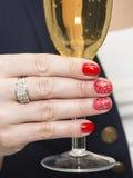 Conception rouge d'art de clou avec un modèle blanc et un verre de champagne Photos stock