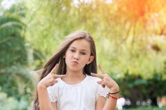 Conception of self-confidence. Flirting little girl making a V s. Ign hand.  Girl in the park Stock Image